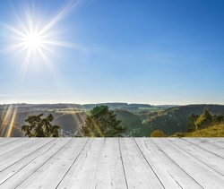 white wooden table top with mountain landscape, blue sky and radiant sun