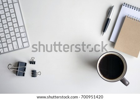 White wooden table with keyboard, pen, notebook, document clips and a cup of coffee. Workspace top view with copy space. #700951420