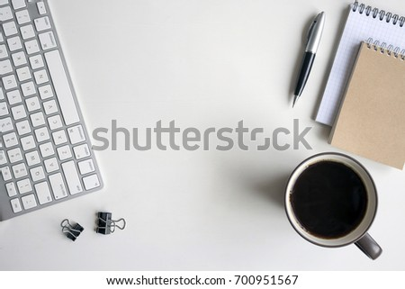 White wooden table with keyboard, pen, notebook, document clips and a cup of coffee. Workspace top view with copy space. #700951567