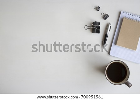 White wooden table with pen, notebook, document clips and a cup of coffee. Workspace top view with copy space. #700951561