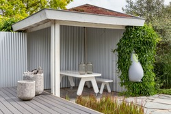 White wooden terrace with natural roof, a pinic bench and a modern water tank