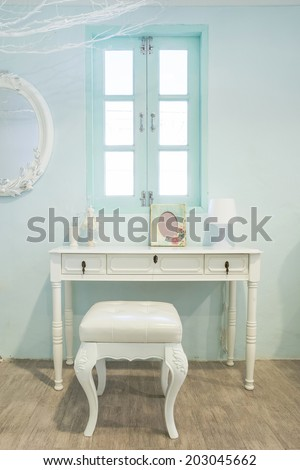 White wooden vanity table with window in background