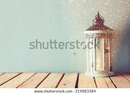 white wooden vintage lantern with burning candle and tree branches on wooden table. retro filtered image with glitter overlay