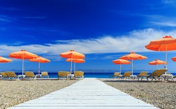 White wooden walkway leading to beach with umbrellas and sunbeds