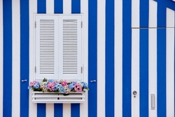 White wooden window of colorful house typical of the city of Aveiro in Portugal.