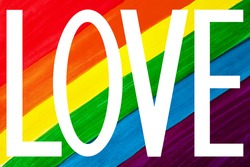 White word LOVE isolated on rainbow colors background close up, LGBT community flag banner, LGBTQ pride poster, letter love sign, gay, lesbian, bisexual etc symbol, trendy watercolor wallpaper design