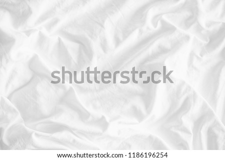 White wrinkled fabic texture rippled surface,Close up unmade bed sheet in the bedroom after night sleep Soft focus.