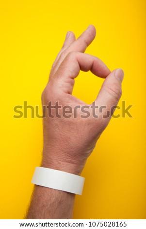 White wristband, bracelet mockup for event, wristlet with sticker.