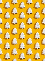 White Xmas tree pattern. Orange seamless background. Festive art ornament composition. Winter holidays symbol. Abstract creative symmetrical arrangement isolated on bright yellow.
