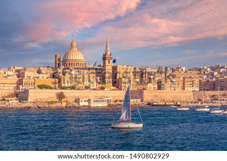 White yacht and Old town of Valletta with churches of Our Lady of Mount Carmel and St. Paul's Anglican Pro-Cathedral at sunset, Valletta, Capital city of Malta Stock photo ©