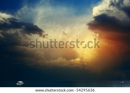 White yacht on sea surface and storm clouds - stock photo