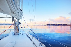 White yacht sailing in a still water at sunset. Frost and first snow on the deck, close-up view to the bow, mast, ropes and sails. Clear blue sky with colorful winter clouds. Norway