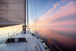 White yacht sailing in an open sea at sunset. Close-up view from the deck to the bow. Clear blue sky with glowing pink clouds reflecting in a still water. Idyllic seascape. Cruise, travel destinations