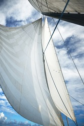 White yacht sails against clear blue sky with lots of clouds. Sailing in an open Mediterranean sea. Idyllic cloudscape. Summer vacations, leisure activity, sport and recreation, private wessel
