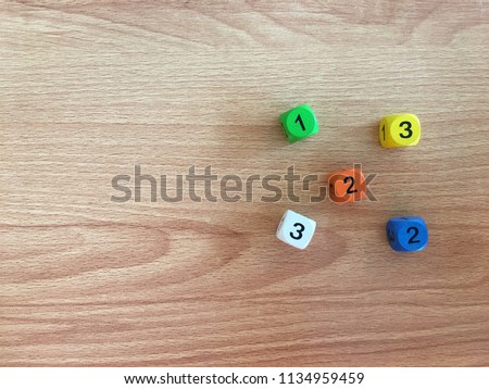 white, yellow, orange, green,blue dics on wooden table from above. Gambling devices. Game of chance concept. #1134959459