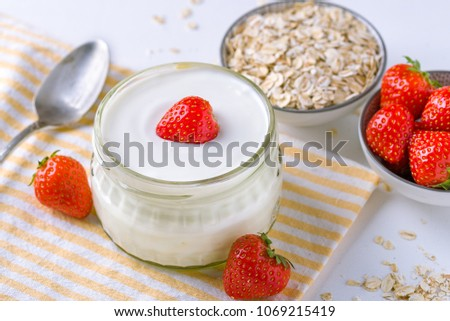 White yogurt in glass bowl with spoon and starwberries on white background. #1069215419