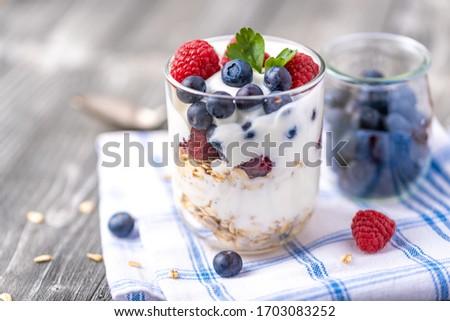 White yogurt in glass jar with raspberries and blueberries on napkin. ストックフォト ©