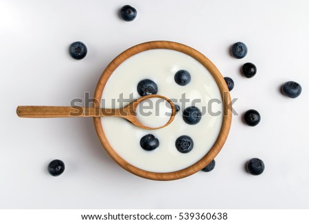 White yogurt in natural wooden bowl with blueberries. Top view. #539360638
