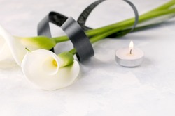White Zantedesia flower tied with a black ribbon, next to a candle on a light background. Copy space. The concept of death, mourning