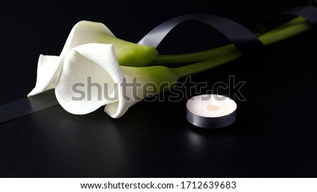 White Zantedesia with mourning ribbon and burning candles on a black background. Concept of sorrow and death ストックフォト ©