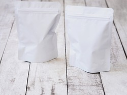 White zipper bag for food packaging. Empty zip package on vintage wooden table.