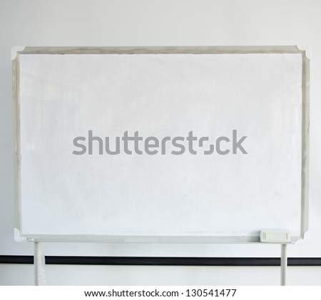 Whiteboard and projector screen in a classroom.