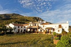 Whitewashed country house with courtyard in the Spanish countryside , Finca Cortijo Las Monjas,Malaga,Andalusia, Spain.Blue sky warm evening at sunset
