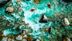 Whitewater kayakers on the Emerald waters of Soca river, Slovenia, are the rafting paradise for adrenaline seekers and also nature lovers, aerial view.