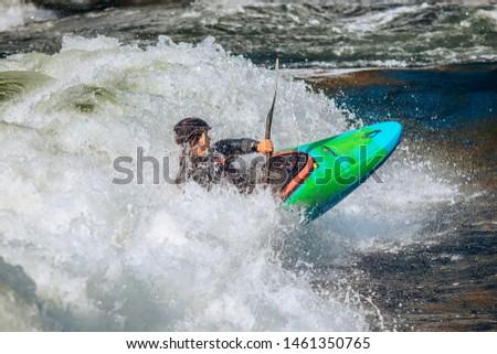 Whitewater kayaking, extreme sport rafting. Guy in kayak sails mountain river.