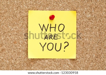 Who Are You written on an yellow sticky note pinned on a cork bulletin board. - stock photo