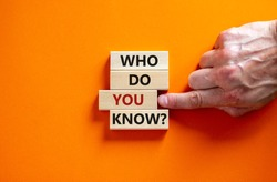 Who do you know symbol. Wooden blocks with words 'who do you know'. Male hand. Beautiful orange background. Business and who do you know concept. Copy space.