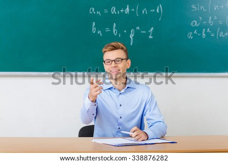 Who is present. Attractive smiling professor is occupied with checking the list of students.