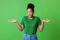Who Knows. Portrait of Funny Young Black Woman Shrugging Shoulders Looking At Camera Posing Over Green Background. Studio Shot. Puzzled lady is clueless. I'm sorry, exuse me, can't decide