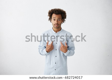 Who, me? Handsome dark-skinned male with Afro hairstyle looking disappointedly at camera pointing at himself with hands being surprised to be choosed by someone isolated over white background