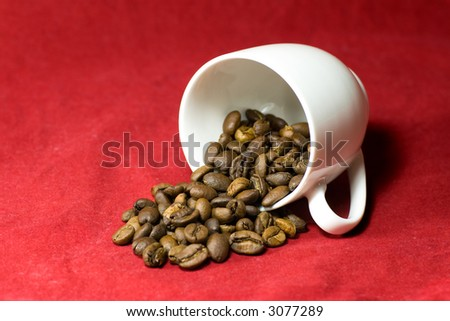 Who spilled the beans? A cup of coffee beans tipped over on a textured red background