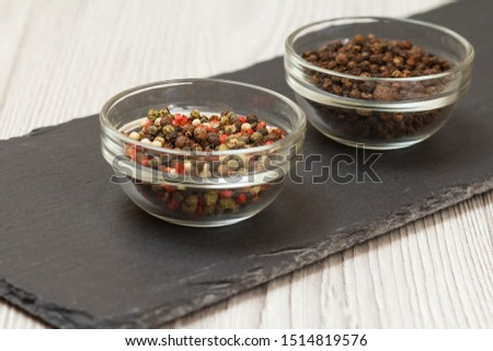 Whole allspice berries in glass bowls on stone cutting board and wooden table. Shallow depth of field. Focus on allspice berries. #1514819576
