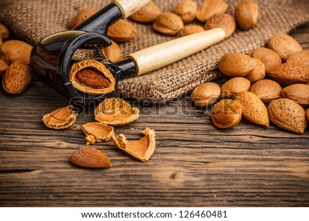 Whole and chopped almonds on vintage wooden background