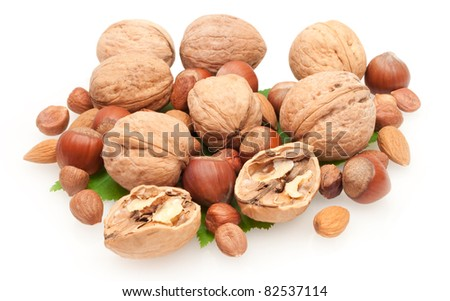 whole and cracked nuts and kernels on green leaves isolated on white background