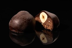 Whole and cut chocolate candy with nut on black background with reflection