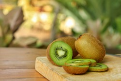 Whole and cut of kiwifruit (Actinidia chinensis) on wooden table with blurred background.Sweet,sour and freshness taste.Have a lot of fiber, vitamins and minerals.Food,Fruits or healthcare concept.