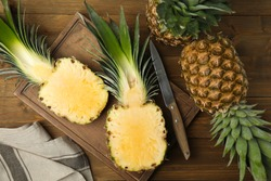 Whole and cut pineapples on wooden table, flat lay