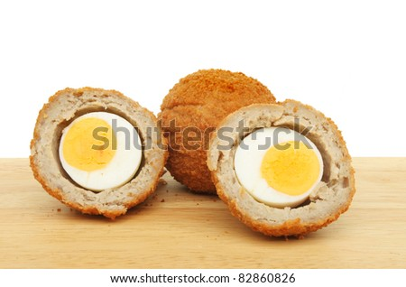 Whole and cut Scotch eggs on a wooden food preparation board
