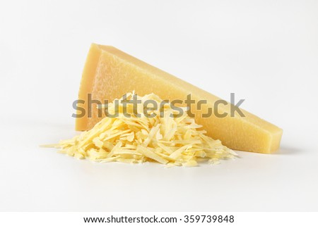 whole and grated parmesan cheese on white background