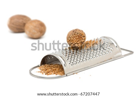 Whole and grind nutmeg with grinder over white background