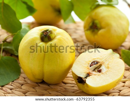 Whole and half quince with leaves on the table