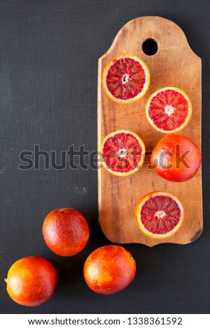 Whole and halved blood oranges on black background, top view. Flat lay, overhead, overhead. Copy space. #1338361592