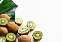 Whole and halved fresh juicy kiwi on large palm tree leaf background with free text copy space. Organic superfood concept for healthy eating