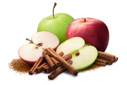 Whole and halved red and green apples next to piles of cinnamon, in sticks and ground. Clipping paths, shadow separated