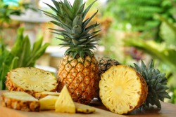 Whole and pieces of Pineapple(Ananas comosus) on wooden table with blurred half,sliced and whole background.Sweet,sour and juicy taste.Have a lot of fiber,vitamins C and minerals.Food,Fruit concept.