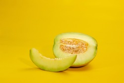 whole and slice of Honeydew Melon, orange melon or cantaloupe melon with seeds isolated on yellow background,selective focus